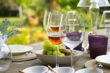 Table, wine glasses, bowl of grapes