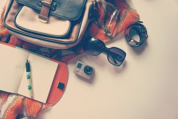 Notebook, pen, camera, sunglasses, bag, shawl, watch